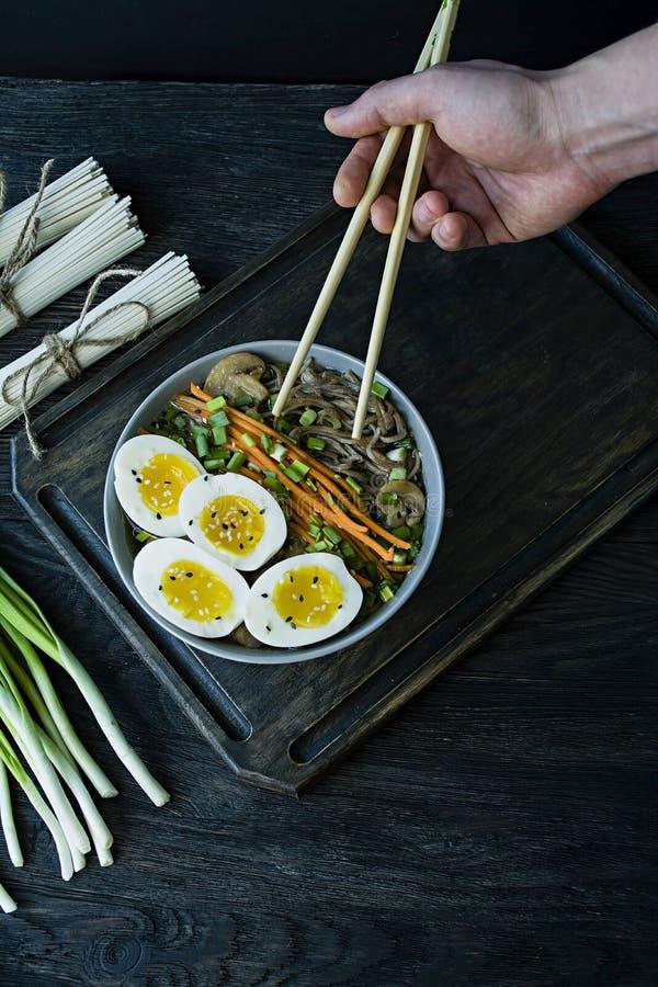 Un homme mange des nouilles de soba de sarrasin avec de la sauce et des garnitures en bouillon Nourriture japonaise Cuisine asiat image stock
