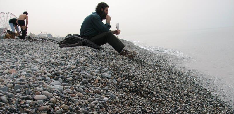 Un homme mange la graine de tournesol sur les plages de caillou de Batumi, la Géorgie photos libres de droits