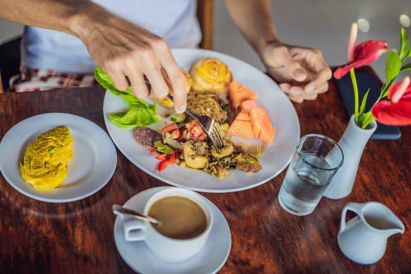 Un homme mange un petit déjeuner asiatique se composant du poulet et des nouilles, photographie stock libre de droits