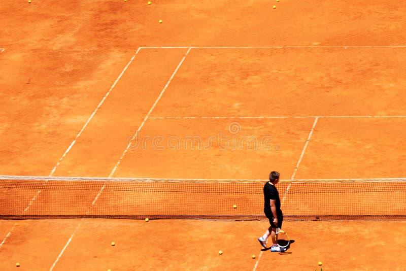 Un homme marchant dans une boule jaune rouge de tennis sur un court de tennis d'argile photo stock