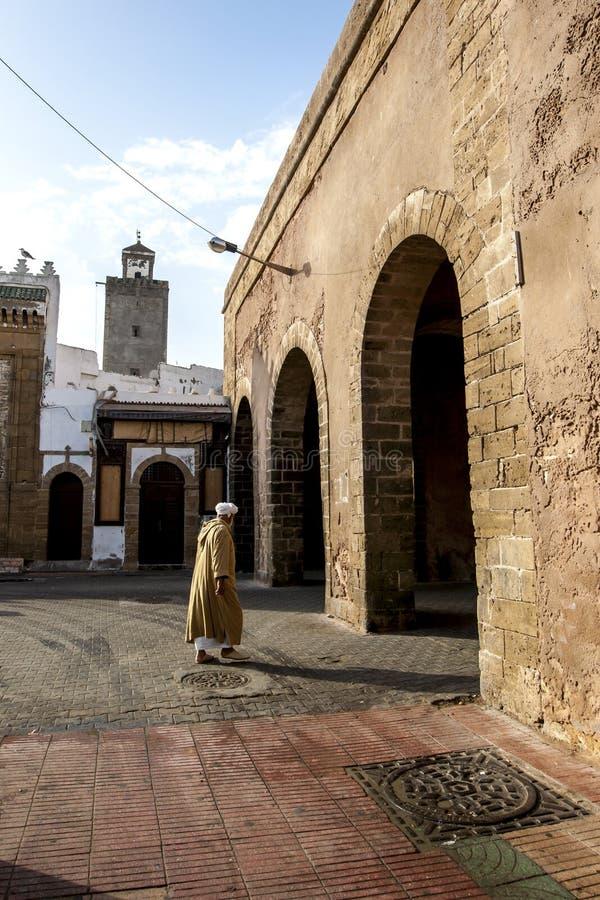 Un homme marchant vers dessus des vieilles portes de ville dans Essaouira au Maroc images libres de droits