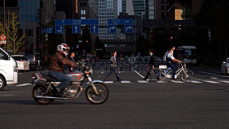 Un homme marche à travers la route à une intersection occupée dans le secteur financier de Tokyo du centre au Japon image stock