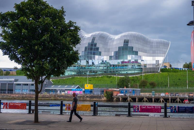 Un homme marche le long du bord du quai de Newcastle Gateshead avec Sage Gateshe photo stock