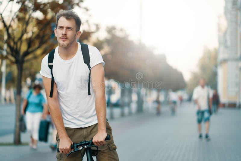 Un homme montant un vélo dans une vieille ville européenne dehors images stock