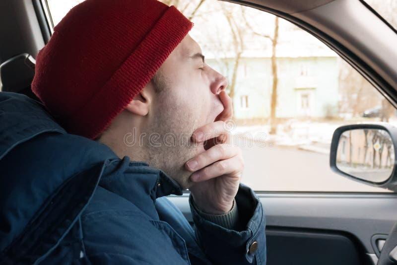 Un homme monte sur la route en hiver, bâillements d'un homme à la roue, fatiguée de l'entraînement images libres de droits
