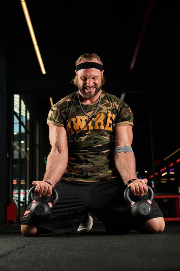 Un homme musclé en uniforme sportif s'agenouille dans la salle de sport avec un effort pour lever la main avec des cloches à boui photo libre de droits
