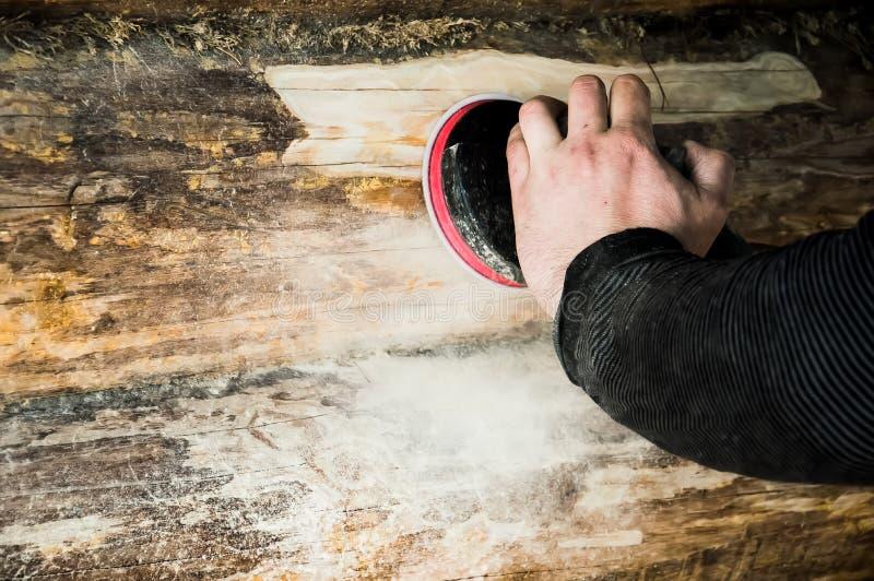 Un homme nettoie les peaux d'un rondin avec une machine de meulage dans une maison en bois photographie stock libre de droits