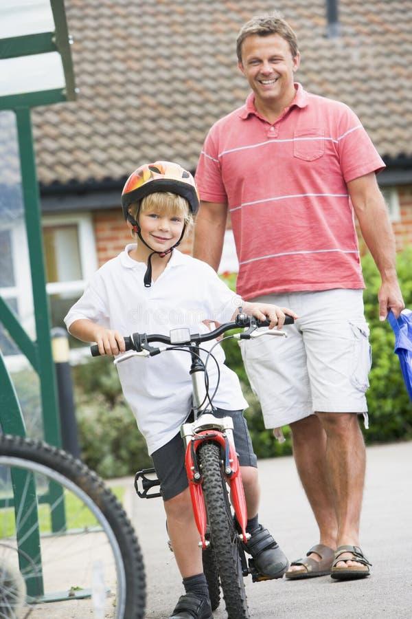 Un homme observant son fils sur une bicyclette images libres de droits