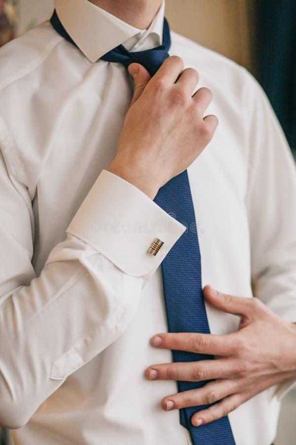 Un homme ou un homme d'affaires dans une chemise blanche met dessus et ajuste le lien bleu images libres de droits