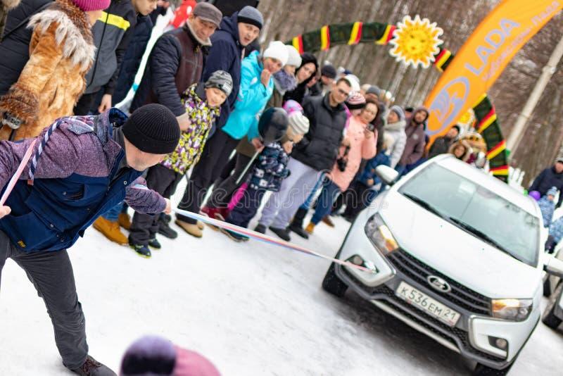 Un homme participe à la concurrence pour les vacances Maslenitsa et traîne une voiture légère de LADA sur une corde Ville de Tche image stock