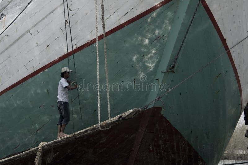 Un homme peignant le bateau en bois photographie stock libre de droits