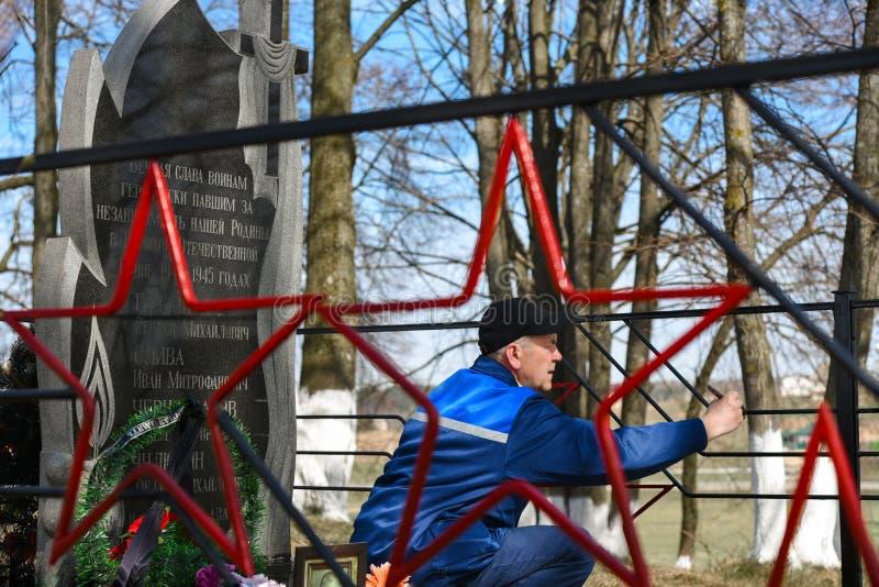 Un homme peint la barrière sur le monument aux soldats soviétiques morts dans la deuxième guerre mondiale photographie stock libre de droits