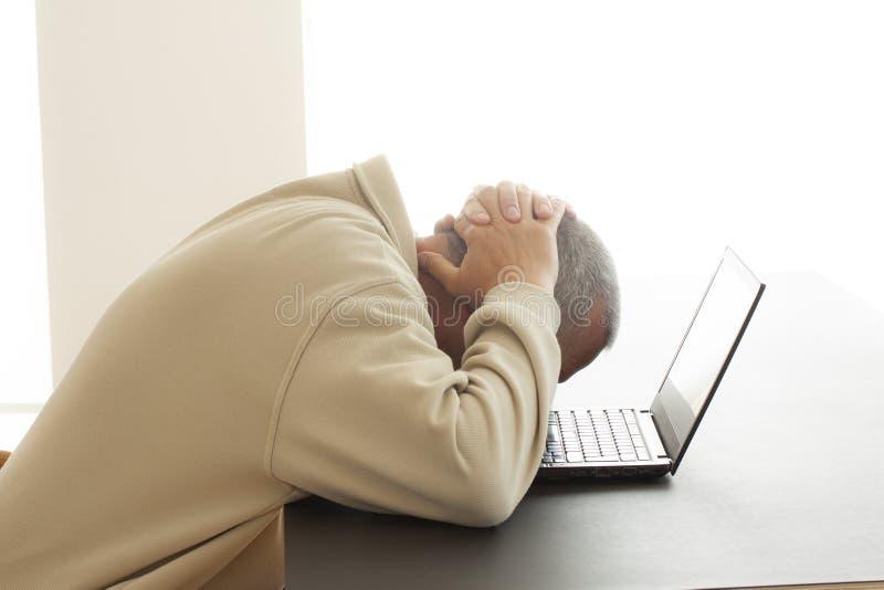 Un homme plie sa tête au-dessus d'un ordinateur de désespoir tandis qu'il met ses mains au-dessus de sa tête - Image photo stock