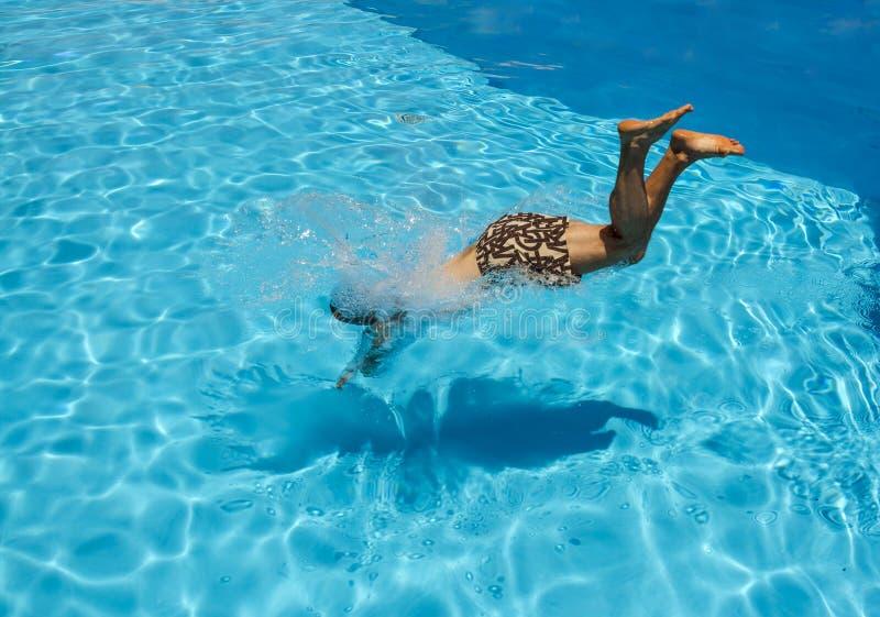 Un homme plonge dans la piscine à la station de vacances images libres de droits