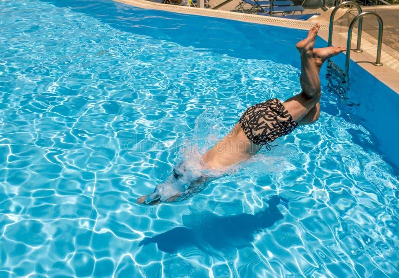 Un homme plonge dans la piscine à la station de vacances photos libres de droits