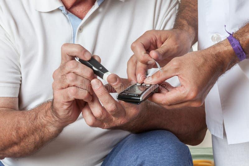 Un homme plus âgé à l'aide du mètre de glucose images libres de droits