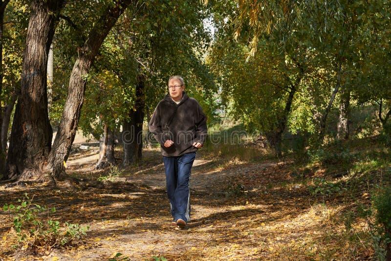 Un homme plus âgé court le long du chemin dans la forêt photo libre de droits