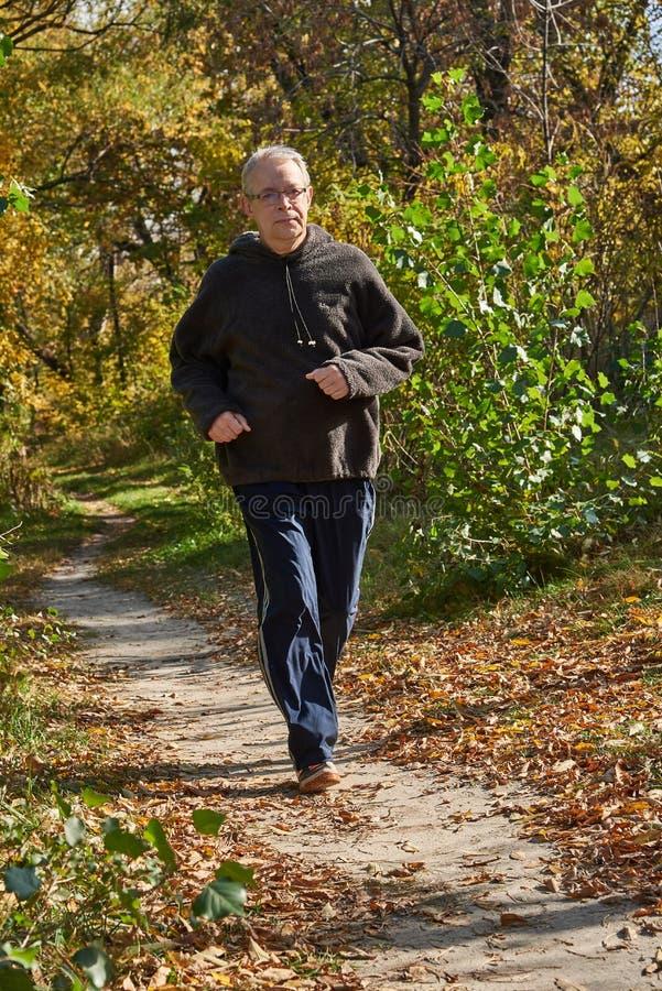 Un homme plus âgé court le long du chemin dans la forêt photographie stock