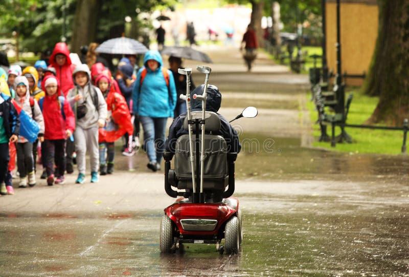 Un homme plus âgé dans un fauteuil roulant mécanique passe par l'alee du parc après un groupe de dépassement d'enfants Sympathie  images stock