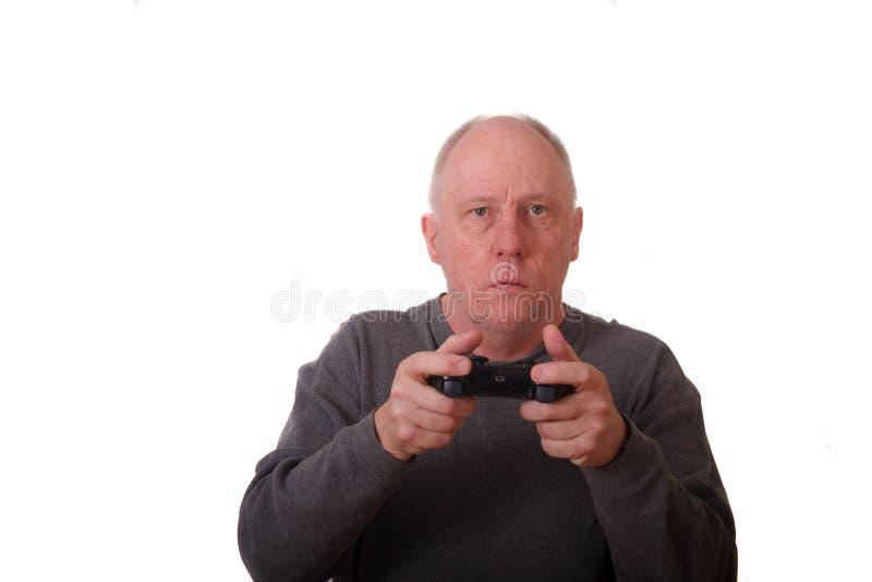 Un homme plus âgé dans la chemise grise jouant le jeu vidéo photos libres de droits