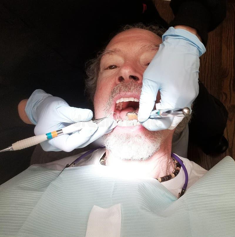 Un homme plus âgé dans le dentiste Chair Getting Teeth a nettoyé photographie stock