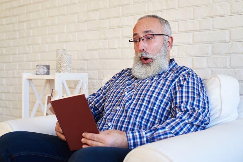 Un homme plus âgé de barbe lisant un livre photos stock