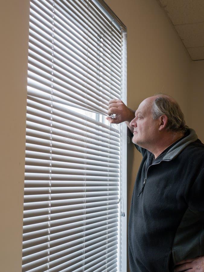 Un homme plus âgé regardant à l'extérieur des abat-jour d'hublot. photos libres de droits
