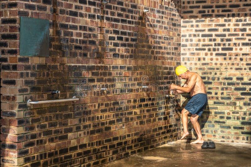 Un homme plus âgé rince des pieds à la douche sur la plage de Bronte, Sydney Australia image stock