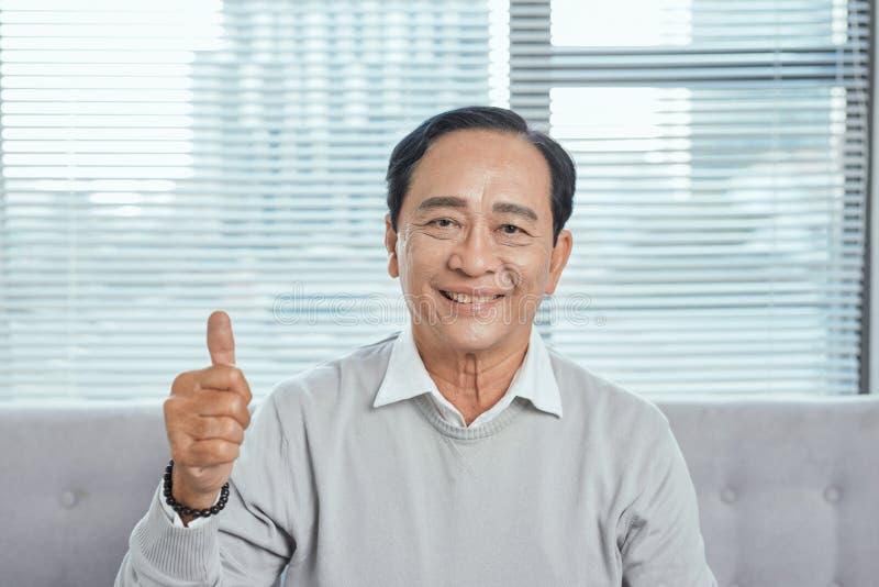 Un homme plus âgé s'asseyant sur le divan renonçant au pouce tout en jouant le jeu d'ordinateur, regardant la caméra, souriant photographie stock libre de droits