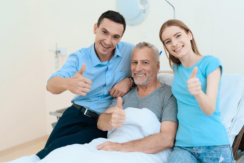 Un homme plus âgé se situe dans une chambre d'hôpital sur un lit Il est vu par un homme avec une femme photos stock