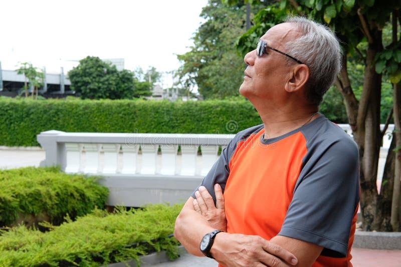 un homme plus âgé se tenant avec des bras croisés pensée pluse âgé de mâle capteur image stock