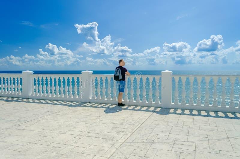 Un homme plus âgé se tient près d'une barrière blanche avec des balustres et des regards à la mer bleue photos stock