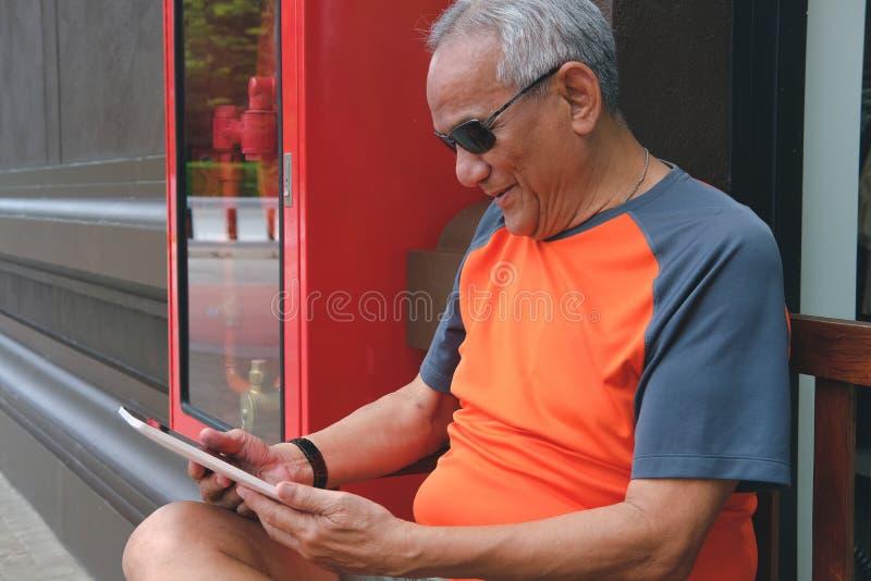 un homme plus âgé tenant le comprimé message textuel masculin supérieur plus âgé, u photo stock