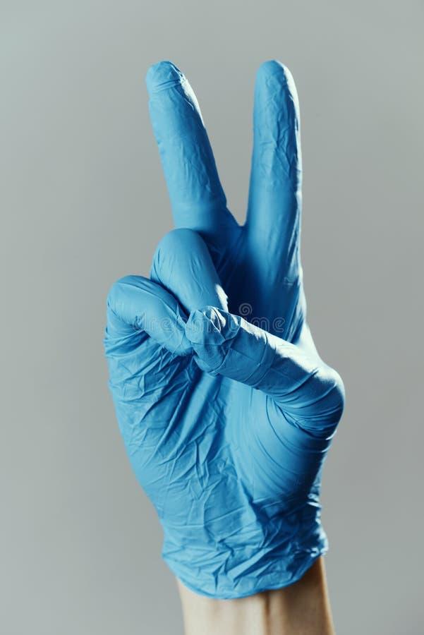 Un homme portant le panneau V portant des gants chirurgicaux image libre de droits