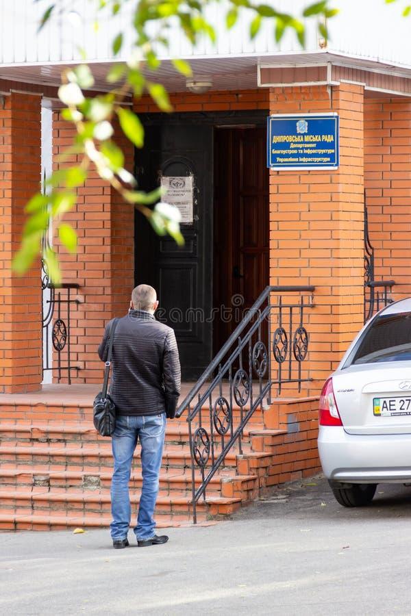 Un homme près de l'entrée au bureau du département de l'aménagement et de l'infrastructure du conseil municipal de Dniprovsky image libre de droits