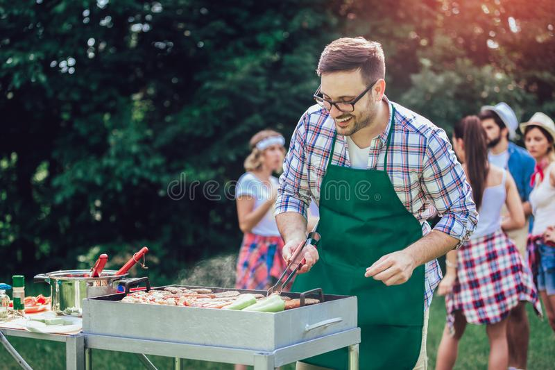 Un homme prépare un barbecue à l'extérieur pour ses amis photos libres de droits