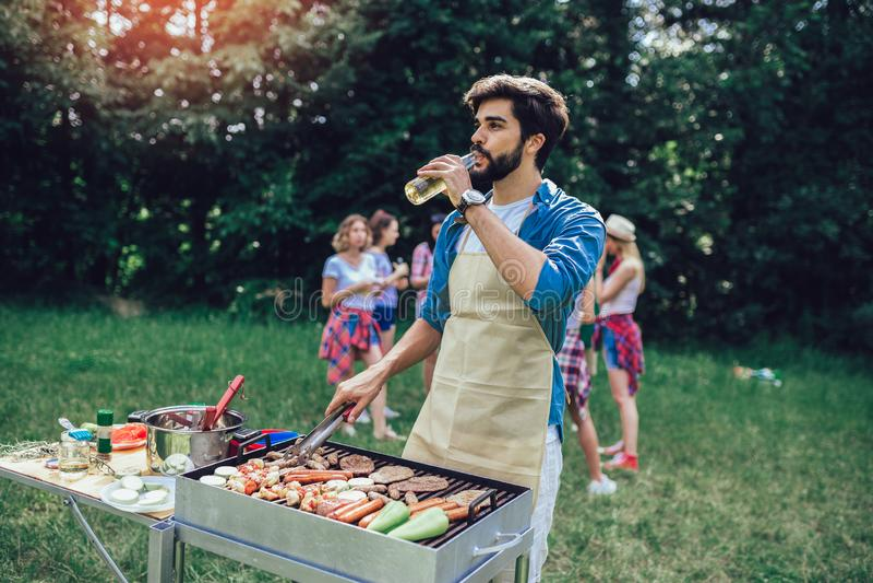 Un homme prépare un barbecue à l'extérieur pour ses amis image stock