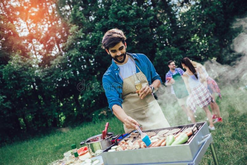 Un homme prépare un barbecue à l'extérieur pour ses amis photographie stock