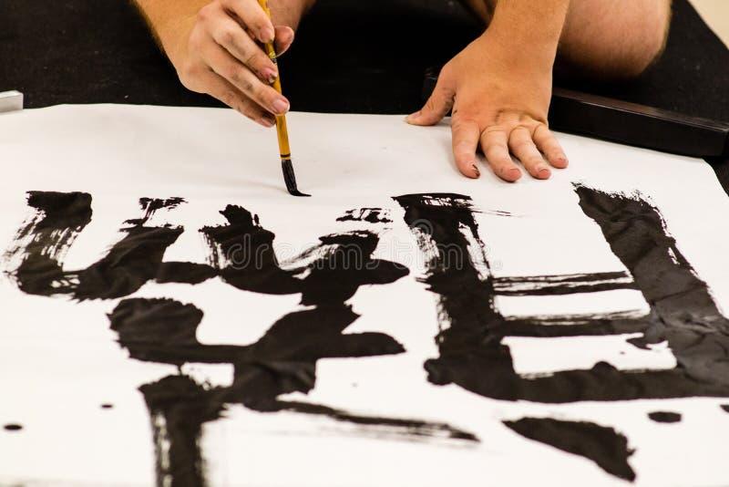 Un homme pratiquant la calligraphie japonaise photographie stock