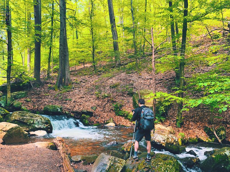 Un homme prenant des photos par un courant à l'intérieur des automnes de Bushkill photographie stock