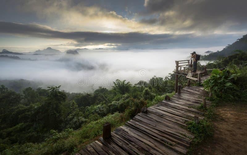 Un homme prenant la photo de la brume sur la crête de montagne pendant le matin, Thaïlande photos stock
