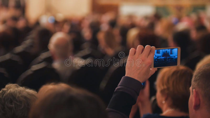 Un homme prend le téléphone dans la salle de concert photographie stock
