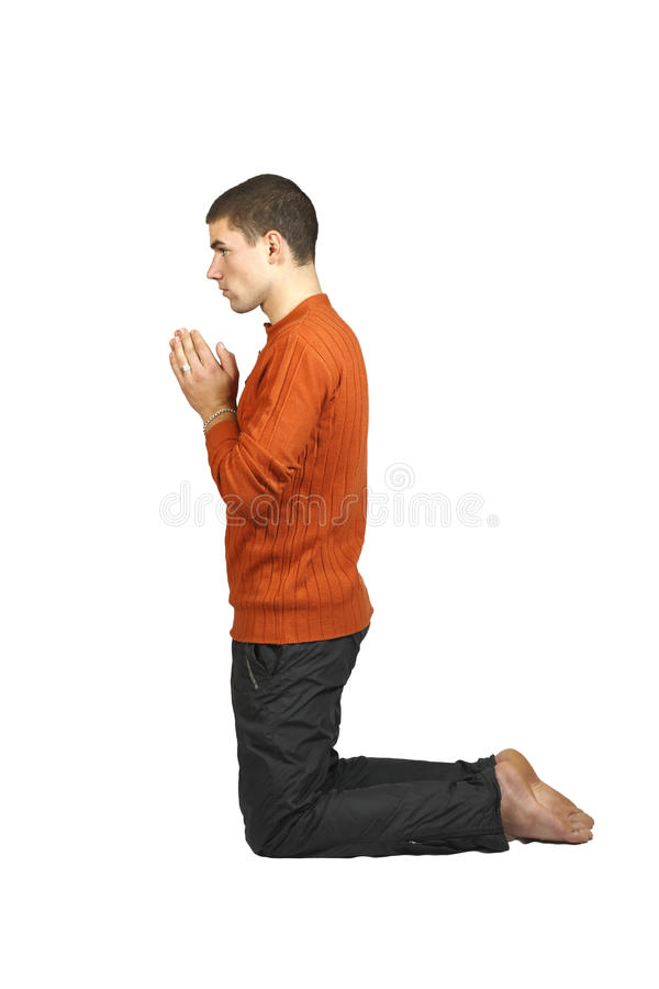 Un homme priant sur ses genoux images stock