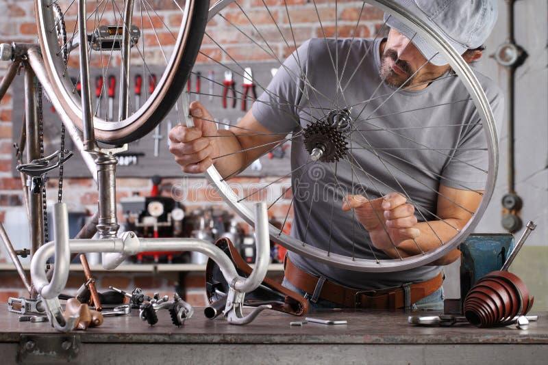 Un homme répare le vélo vintage dans un atelier de garage sur le pupitre avec des outils, un concept de bricolage photo stock