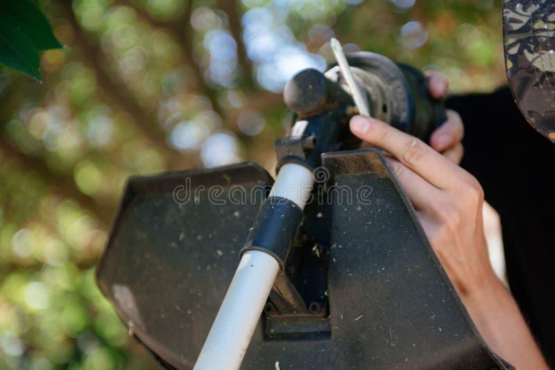 Un homme répare un trimmer Un homme répare une tondeuse à gazon en plan rapproché photos stock