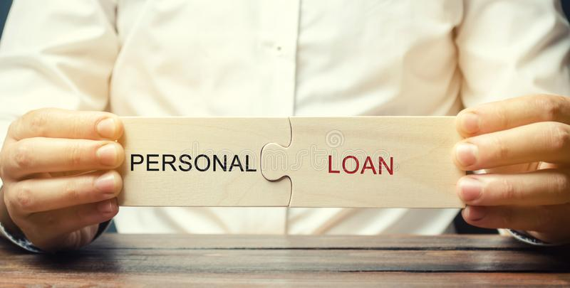 Un homme rassemble des puzzles en bois avec le prêt personnel de mot Un prêt a fourni par une banque aux personnes pour le consom images libres de droits