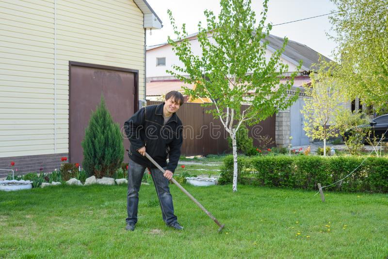 Un homme ratisse le vieux feuillage sur une pelouse d'herbe verte ? son cottage d'?t? photo libre de droits