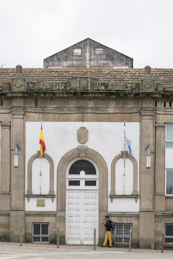 Un homme regarde son téléphone portable devant la façade d'une école d'Etat images stock
