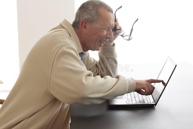 Un homme repose rire fort avec la bouche ouverte pendant qu'il indique l'écran d'un ordinateur portable Il lit ou voit quelque ch photographie stock