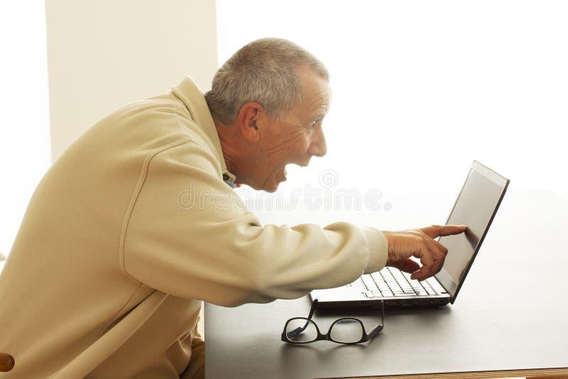 Un homme repose rire fort avec la bouche ouverte pendant qu'il indique l'écran d'un ordinateur portable Il lit ou voit quelque ch photo stock